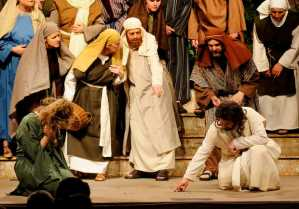 "In a scene from East Auburn Baptist Church production of ""The Event,"" Jesus, portrayed by Shawn DeGraff, writes in the dirt and asks the accusers, ""He who is without sin, let him cast the first stone,"" when a woman caught in the act of adultery is brought before him, portrayed by Lisa Roy."